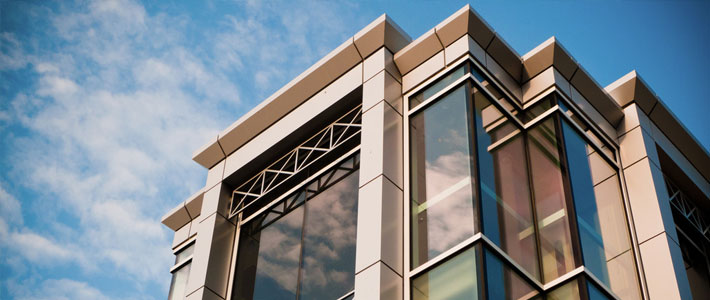 Low Angle View of Metal and Glass Office Building Against Blue Sky and White Clouds